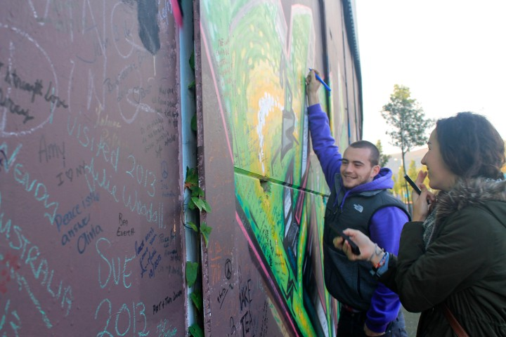 """A """"peace wall"""" has separated the two sides in Belfast since 1969. Visitors leave their mark on the wall with words of encouragement."""