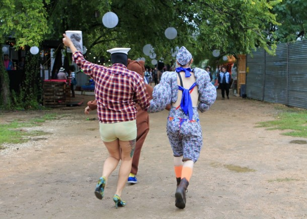 Two festivalgoers skip around puddles after the rain clears at Stargayzer Festival at Pine Street Station. Photo by Alex Vickery