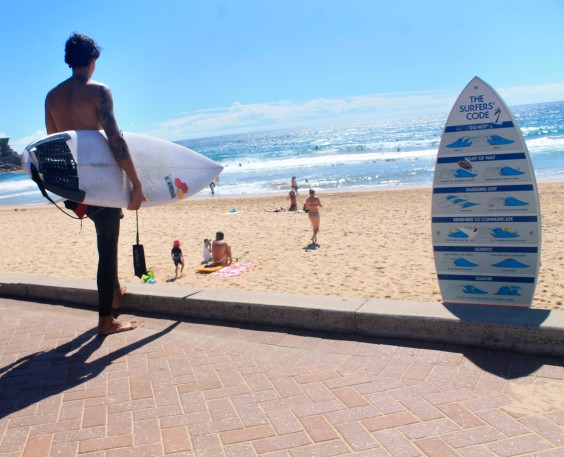 A surfer stares at the waves at Manly Beach.